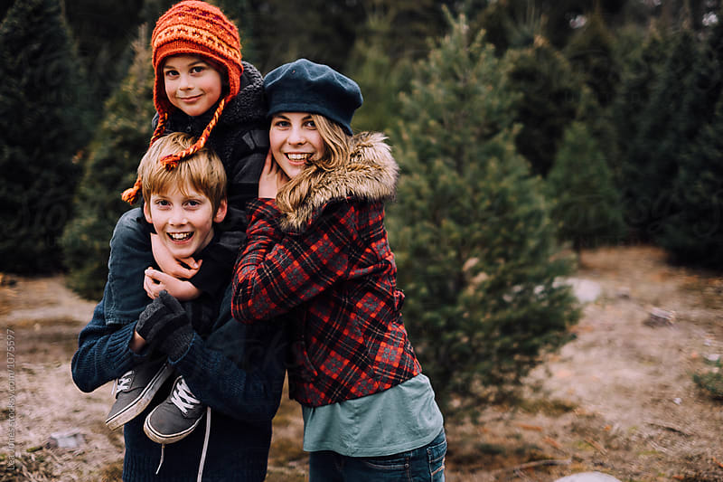 children posing for Christmas card at tree farm by Léa Jones for Stocksy United