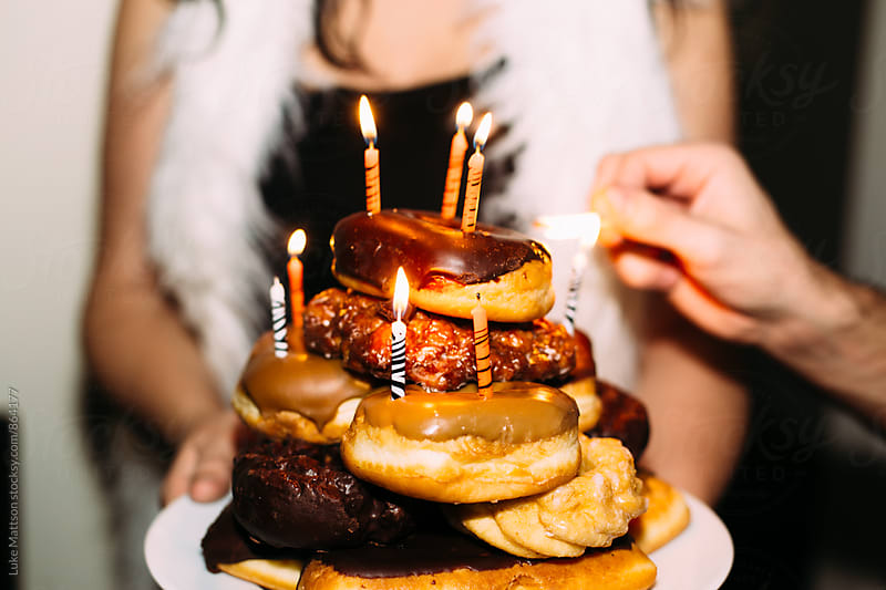 Tower Of Donuts With Burning Candles On Serving Plate Resembling Birthday Cake by Luke Mattson for Stocksy United