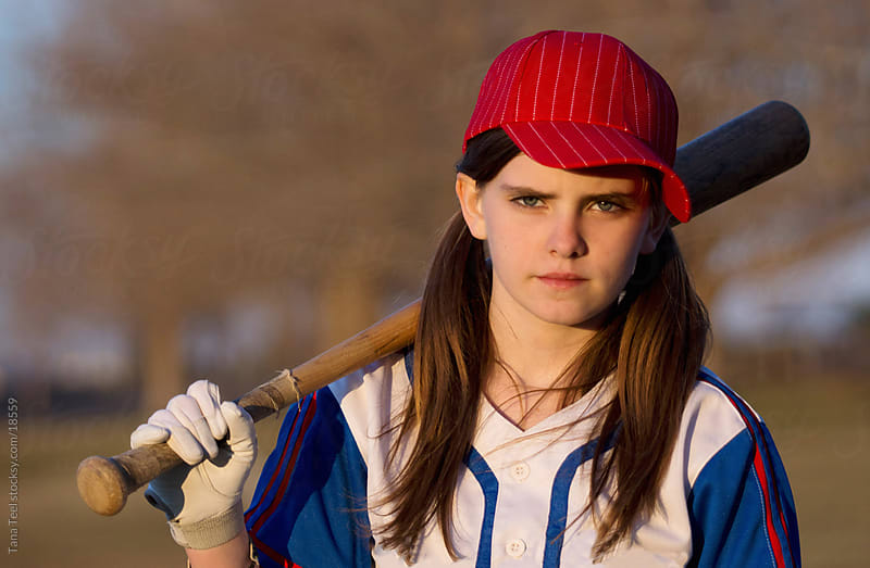 Young girl with baseball bat on her shoulder.  by Tana Teel for Stocksy United