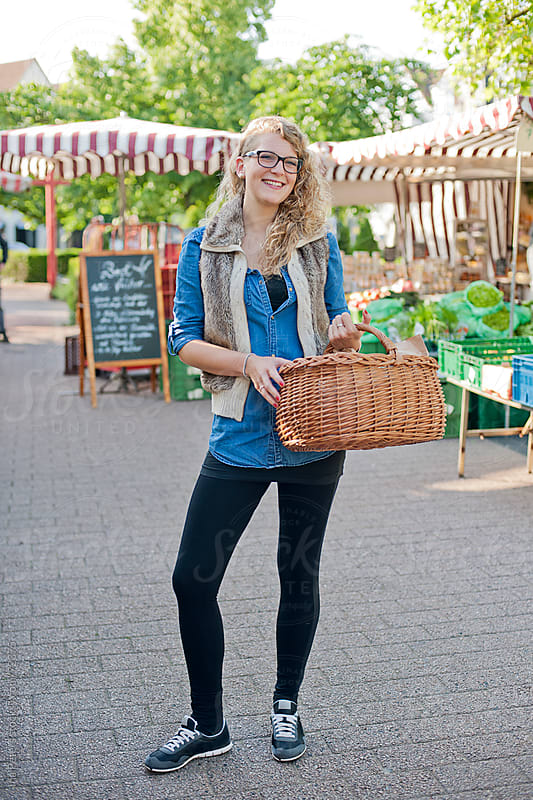 Young woman with shopping basket at a small farmer's market by Ina Peters for Stocksy United