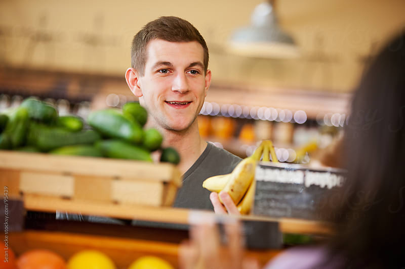Market: Young Man Flirts With Woman In Produce Area by Sean Locke for Stocksy United