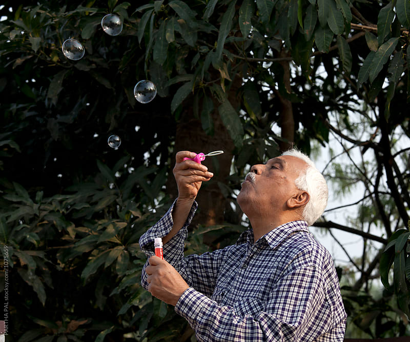 Aged man playng with water bubbles by PARTHA PAL for Stocksy United