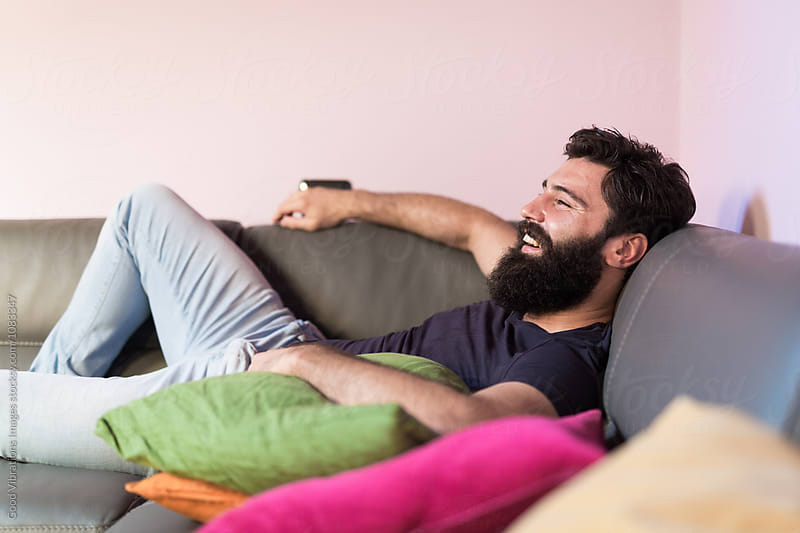 Bearded man relaxing on the sofa by Good Vibrations Images for Stocksy United