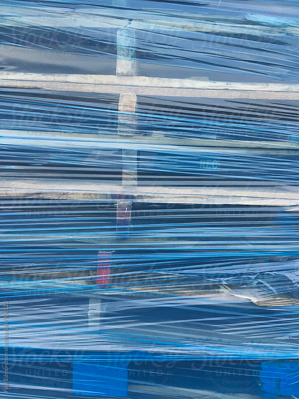 Stack of wood pallets covered in blue plastic wrap by Paul Edmondson for Stocksy United