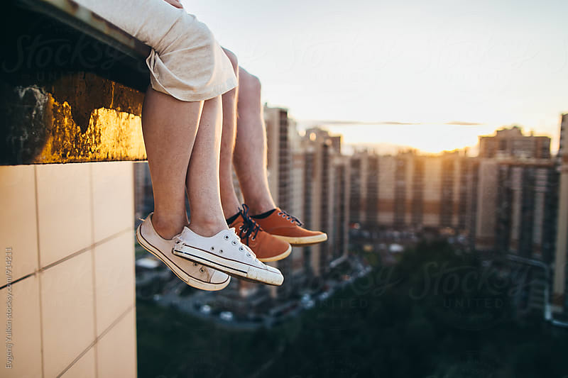 Couple dangling their legs over the edge of rooftop by Evgenij Yulkin for Stocksy United