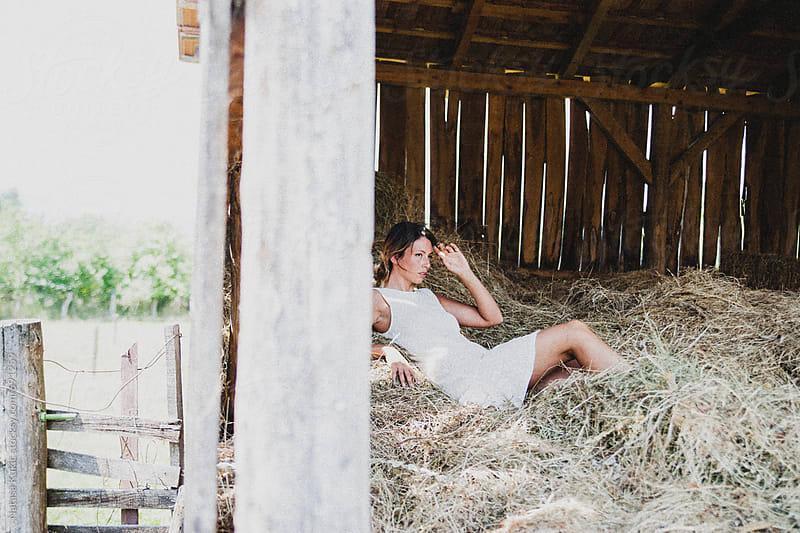 Portraits of a beautiful young woman lying in a hay by Natasa Kukic for Stocksy United