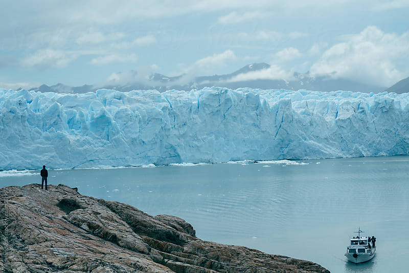 Man and boat at the Perito Moreno Glacier by Adrian Seah for Stocksy United