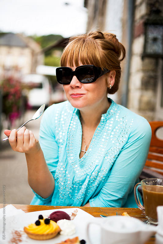 Woman enjoying a pastry. by IDS Photography for Stocksy United