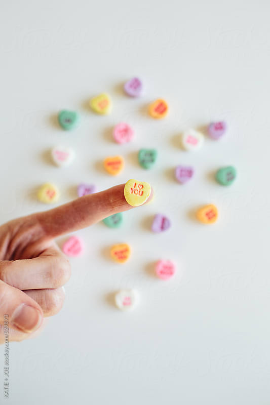 Valentine's Day candy sweet hearts in a hand by KATIE + JOE for Stocksy United