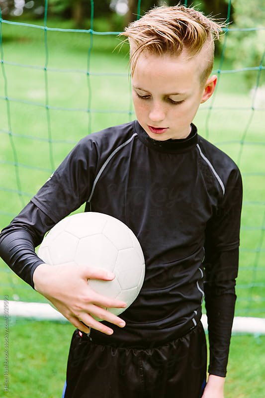 Teenage boy dressed for football training and holding a football.  by Helen Rushbrook for Stocksy United