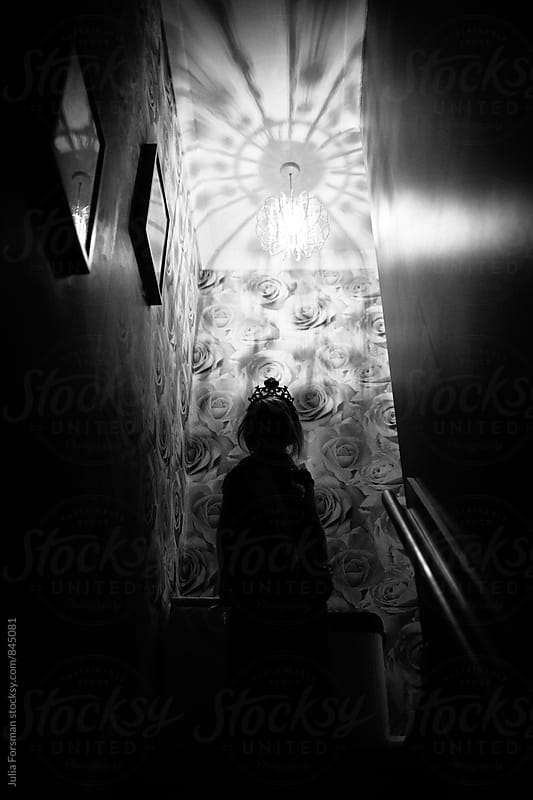 An anonymous child wearing a tiara at the top of a staircase covered in rose wallpaper. by Julia Forsman for Stocksy United