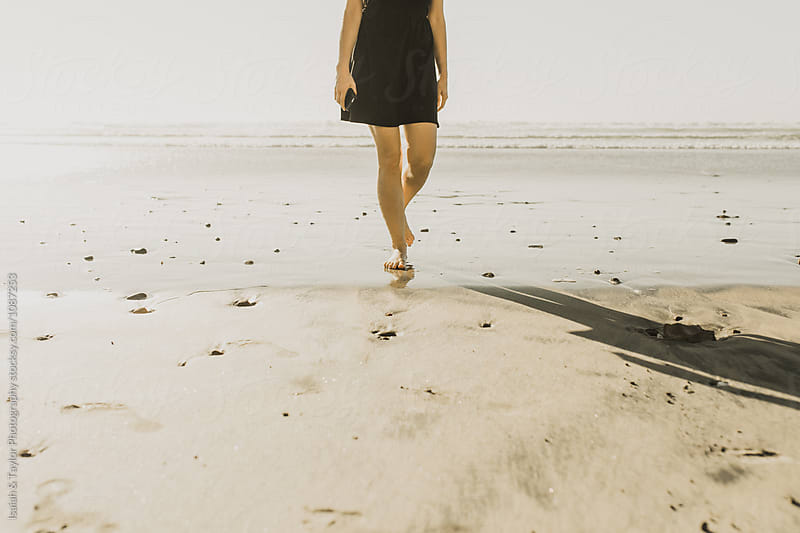 Girl walking on beach by Isaiah & Taylor Photography for Stocksy United