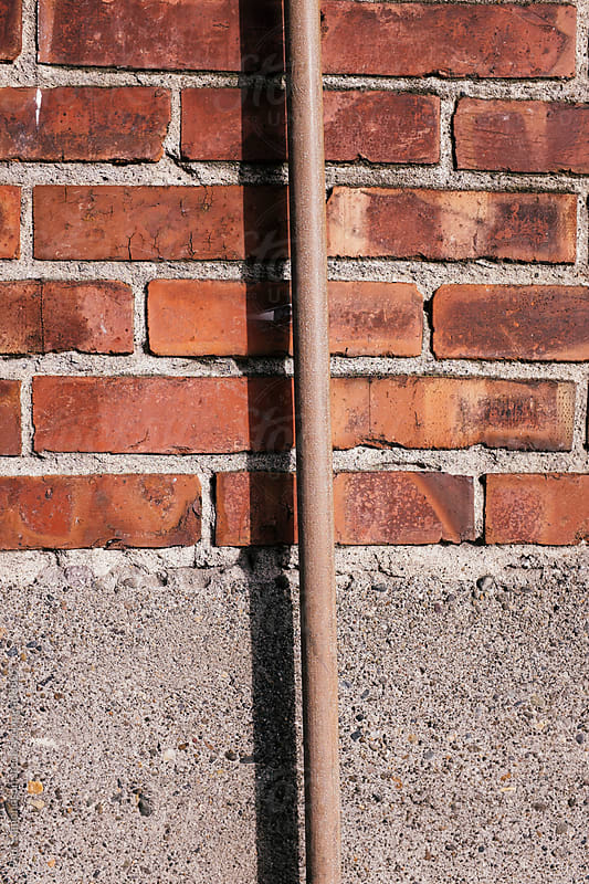 Old brick wall and metal pipe, close up by Paul Edmondson for Stocksy United