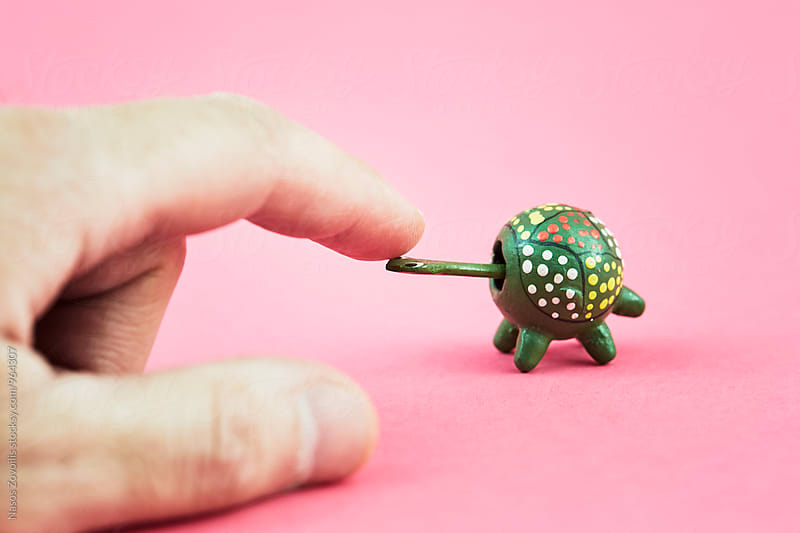 Man's hand playing with a toy turtle  by Nasos Zovoilis for Stocksy United