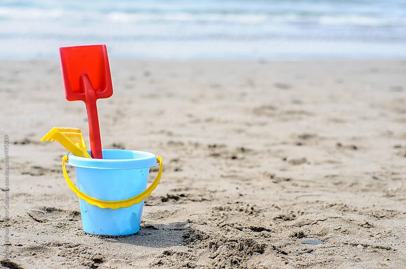 Rake shovel bucket on the beach by Marta Muñoz-Calero Calderon for Stocksy United