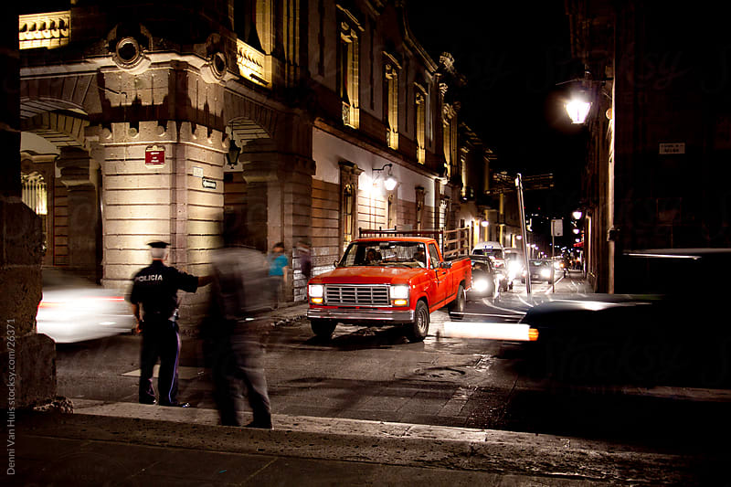 Busy street at night time controlled by a police man by Denni Van Huis for Stocksy United