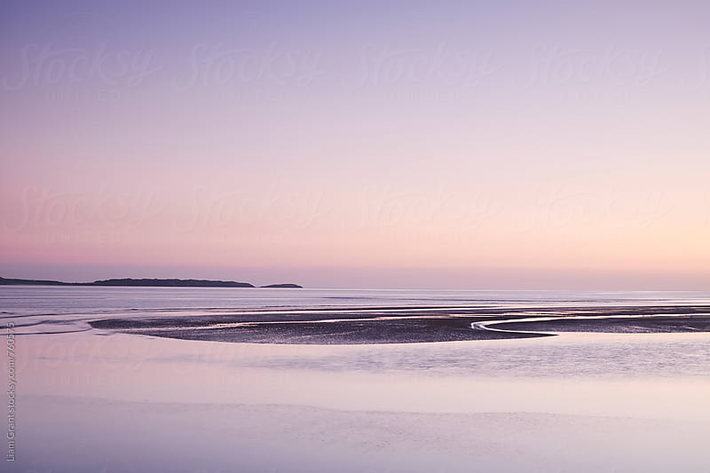Colourful twilight sky at low tide. Burry Port, Wales, UK. by Liam Grant for Stocksy United