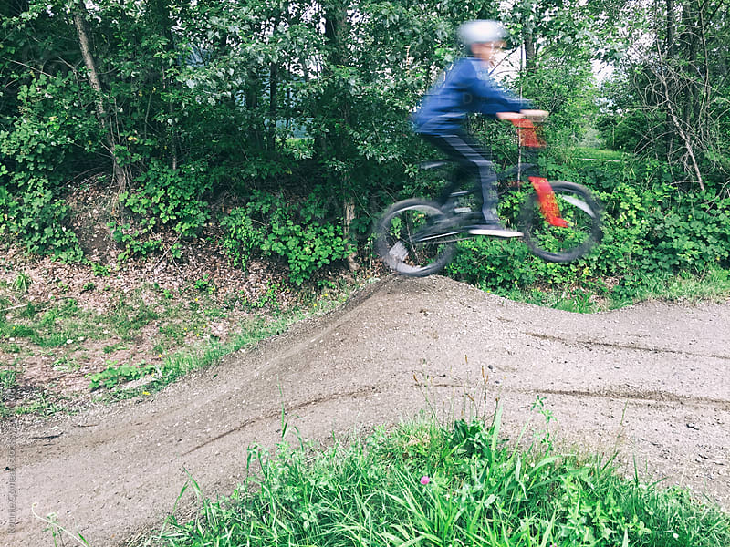Boy Jumping Bike At BMX Track by Ronnie Comeau for Stocksy United