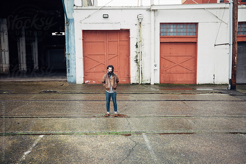 Portrait of a young man standing in front of old car garages by Mihael Blikshteyn for Stocksy United