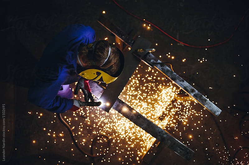 fire splashes illuminating metal worker with plasma cutter from above by Leander Nardin for Stocksy United