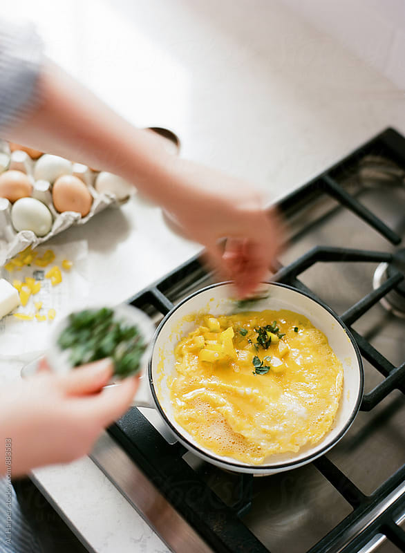 Woman cooking an omelette by Ali Harper for Stocksy United