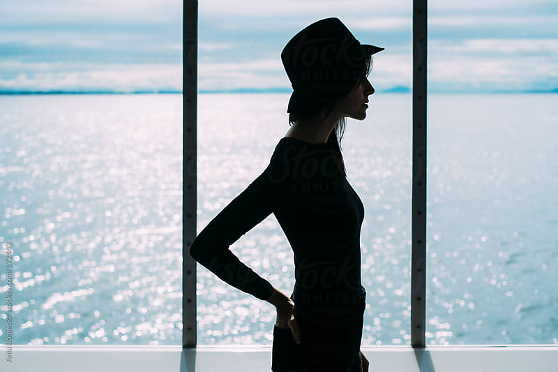 Silhouette of a woman standing in front of a window facing the ocean by Ania Boniecka for Stocksy United