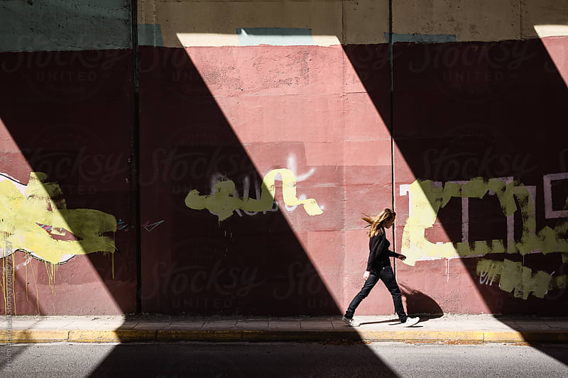 Woman Walks Through Alternating Sun and Shadow by Helen Sotiriadis for Stocksy United
