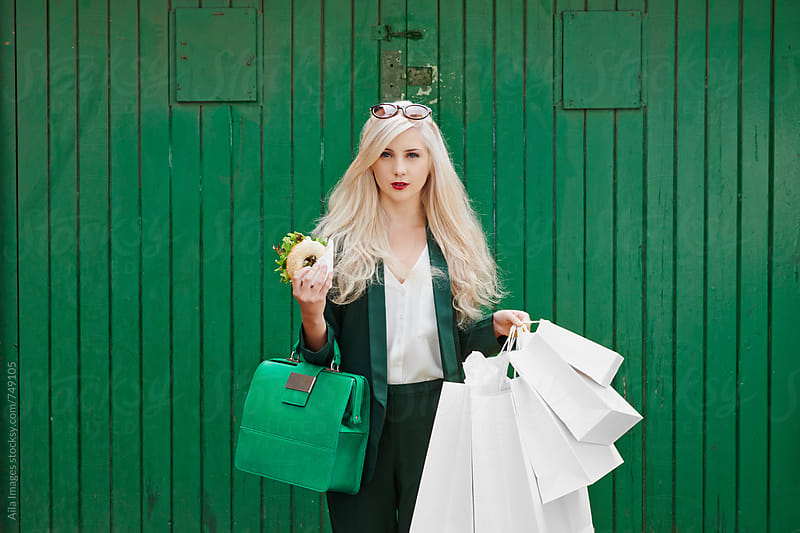 Smart woman in Green Suit shopping with her lunch snack by Aila Images for Stocksy United
