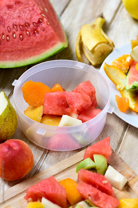 preparing lunch box of fruit salad by Juan Moyano for Stocksy United