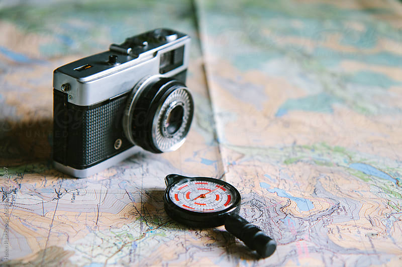 Vintage camera and opisometer on a map. by Helen Rushbrook for Stocksy United