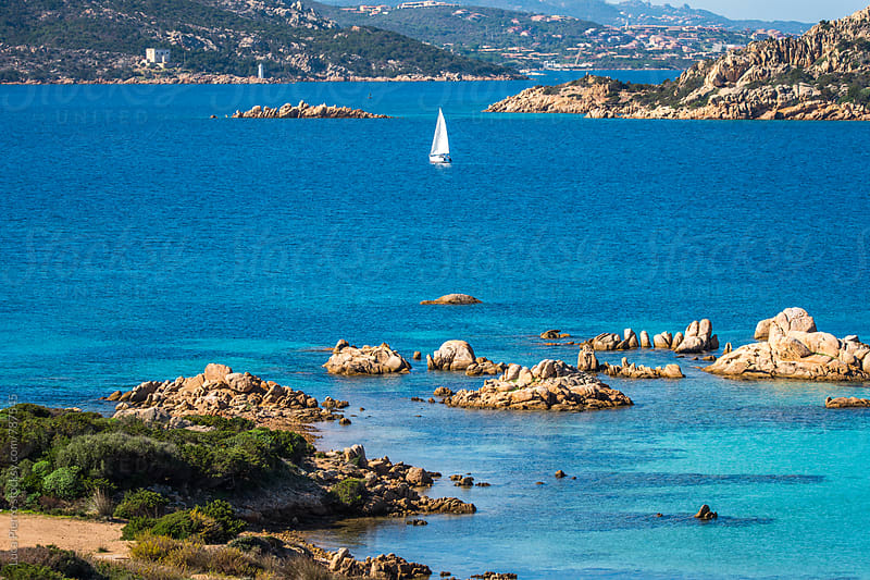 White sail boat along La Maddalena Island coast by Luca Pierro for Stocksy United