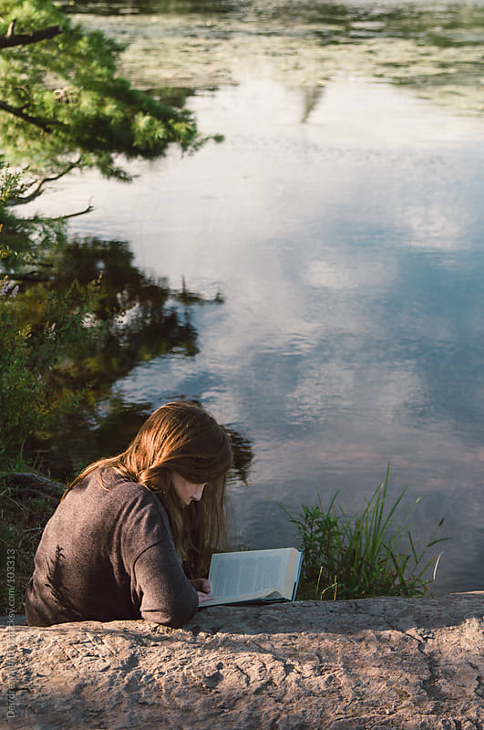 girl reading book on rock by lake by Deirdre Malfatto for Stocksy United