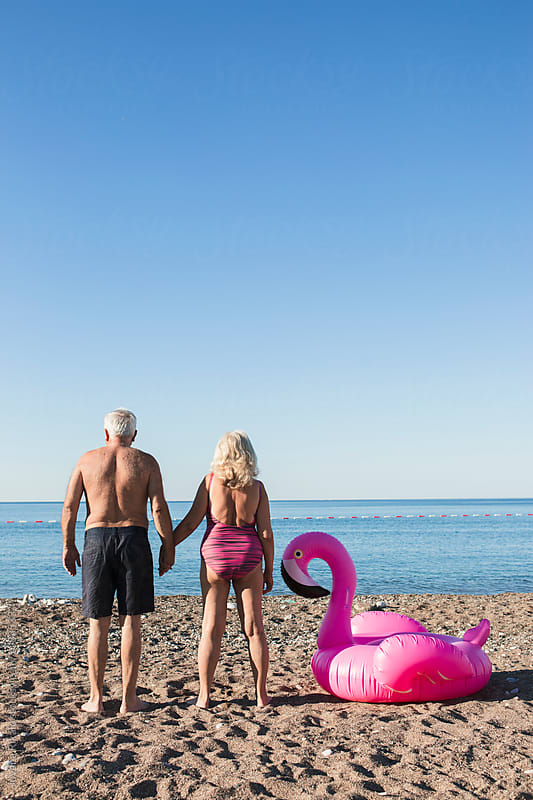 Elderly couple and a flamingo float on the beach by Jovana Rikalo for Stocksy United