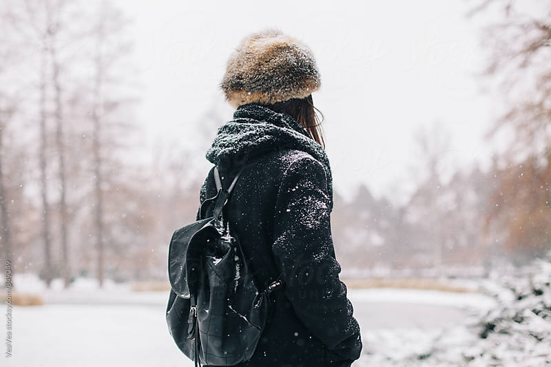 Woman standing in the park during a snowy day by VeaVea for Stocksy United