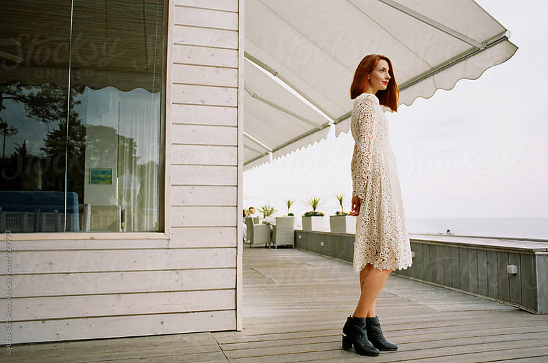 Young redhead woman posing outdoors by Lyuba Burakova for Stocksy United