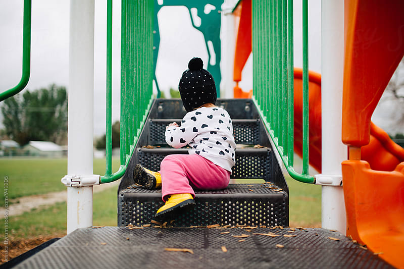 Toddler girl climbing on steps at playground by Jessica Byrum for Stocksy United