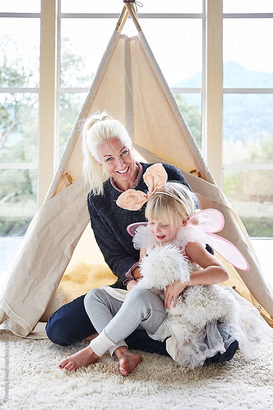 Mom and daughter playing in front of teepee in living room by Trinette Reed for Stocksy United