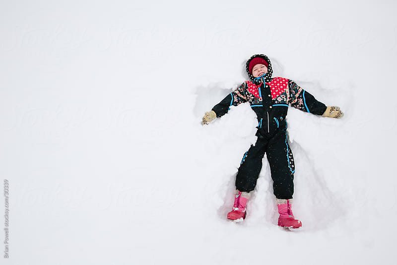 a little girl making a snow angel by Brian Powell for Stocksy United