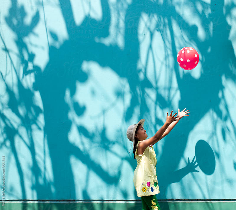 Girl playing with a red balloon by PARTHA PAL for Stocksy United