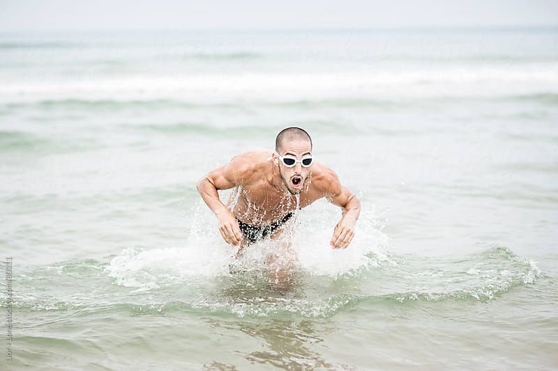 Athlete training for triathlon at sea by Lior + Lone for Stocksy United