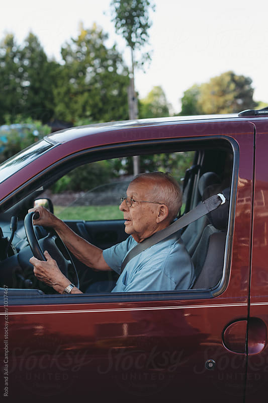 Concentrating senior man driving minivan by Rob and Julia Campbell for Stocksy United