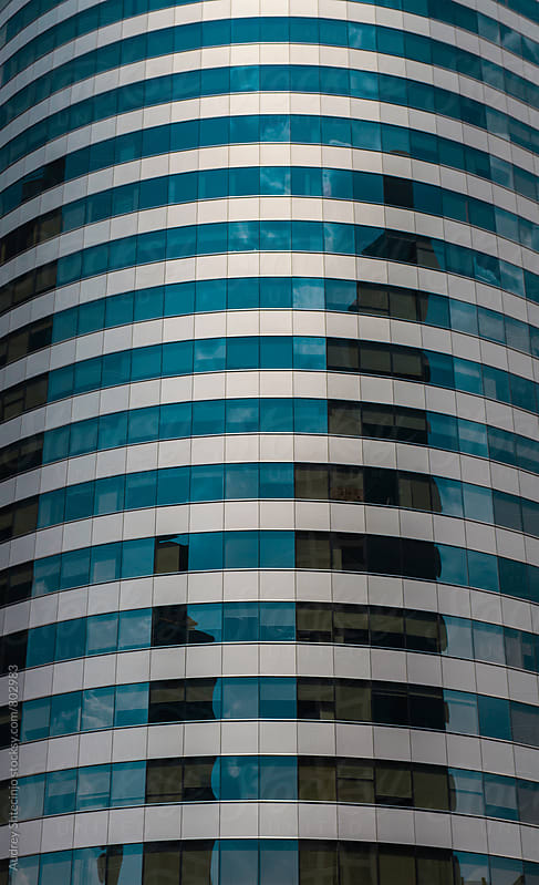 Curved glass corporate building in business district/detail by Marko Milanovic for Stocksy United