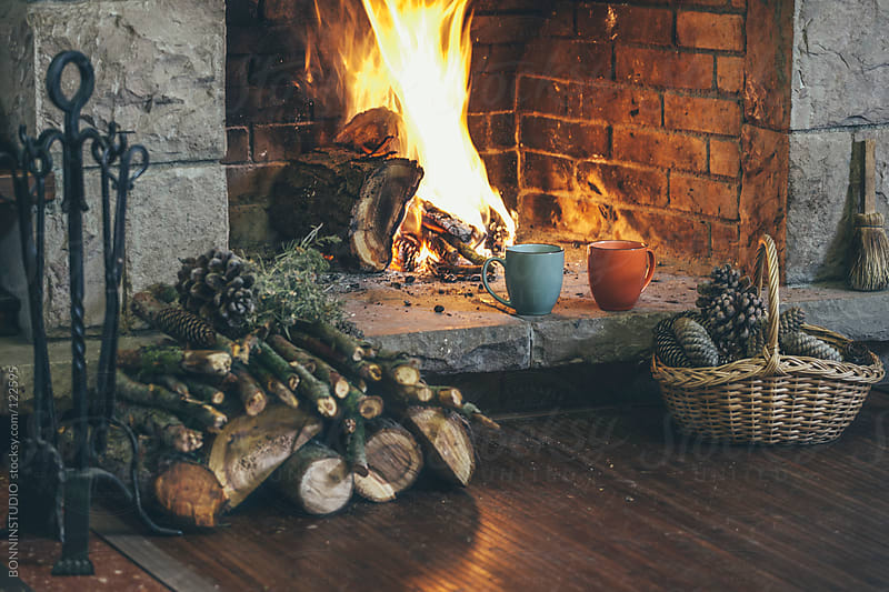 Fireplace in a comfortable home. Woodpile, basket of pine cones and two hot cups. by BONNINSTUDIO for Stocksy United
