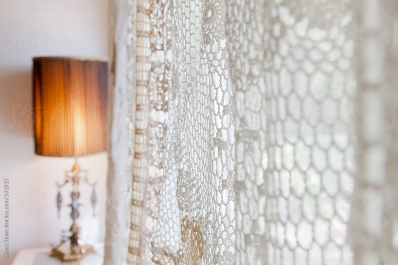 Lamp and crochet drapes by Carey Shaw for Stocksy United