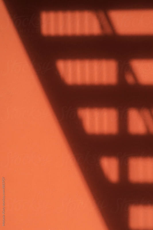 Diagonal shadow of a staircase cast on an orange wall by Melanie Kintz for Stocksy United