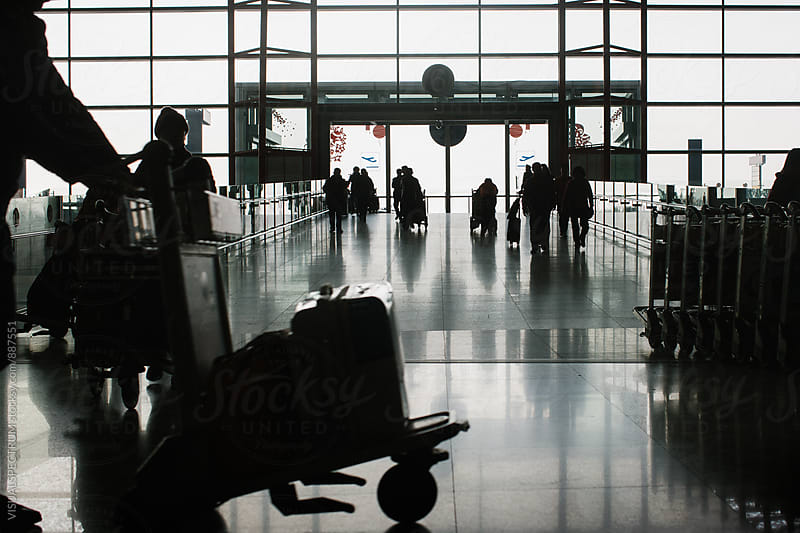 Silhouette of Travelers with Luggage in Airport by Julien L. Balmer for Stocksy United