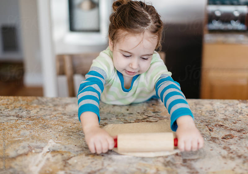 Toddler rolling dough with a rolling pin by Jakob for Stocksy United