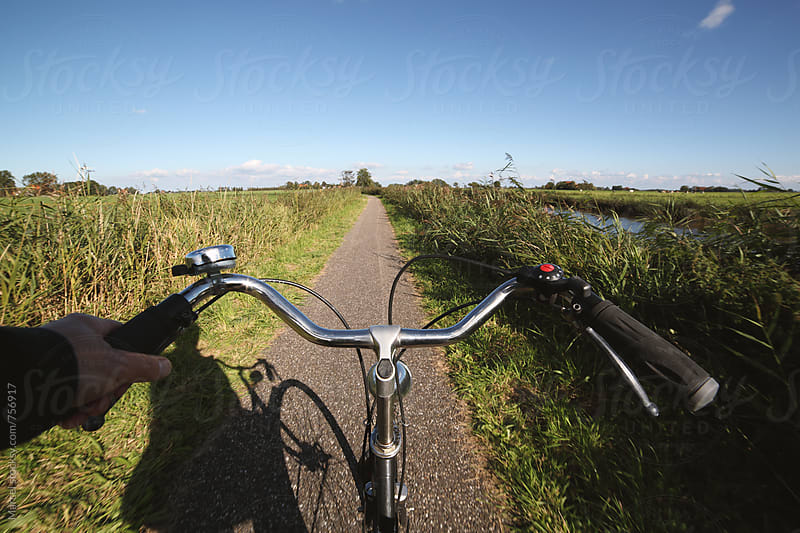 Man cycling between river and meadows by Marcel for Stocksy United