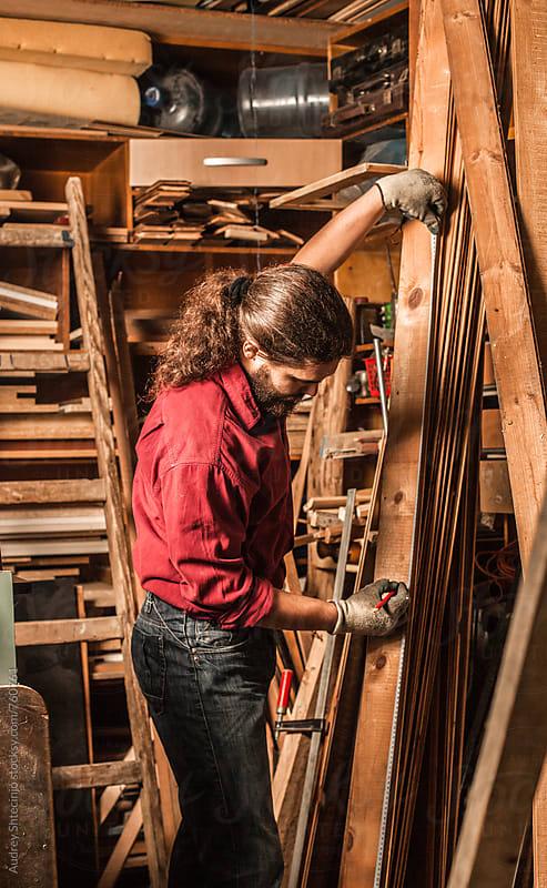 Male carpenter measuring wooden boards . by Audrey Shtecinjo for Stocksy United