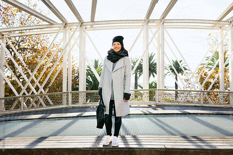 Asian woman standing in the city on winter. by BONNINSTUDIO for Stocksy United